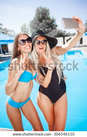 Cheerful girl are standing and making selfie near a swimming pool. They are showing peace sign and smiling. The friends are embracing - stock photo