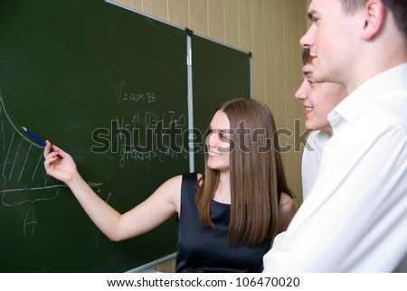 Cheerful girl at a board shows on the schedule. - stock photo