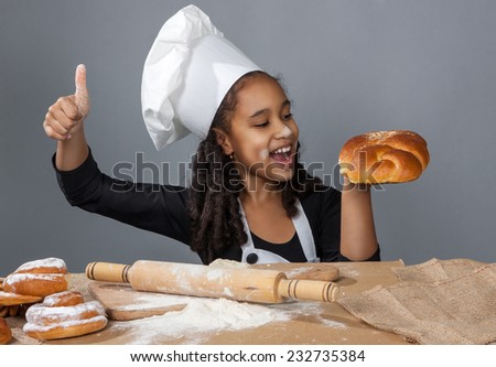 cheerful girl chef giving a thumbs up gesture of approval an success - stock photo