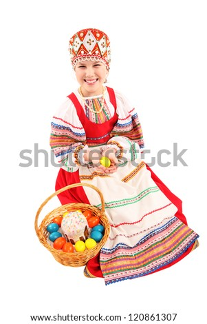 Cheerful girl dressed in traditional dress. She holds the basket with Easter eggs and a holiday cake.