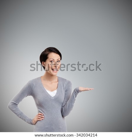 Cheerful girl gestures pointing hand, isolated on grey - stock photo