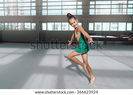 cheerful girl gymnast performs a dance in rhythmic gymnastics - stock photo
