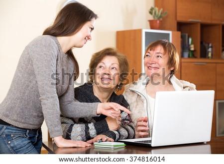 Cheerful girl helping senior women buy something in web - stock photo