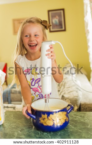 cheerful girl helps her mother in the kitchen, she whips the batter in the pan mixer  - stock photo