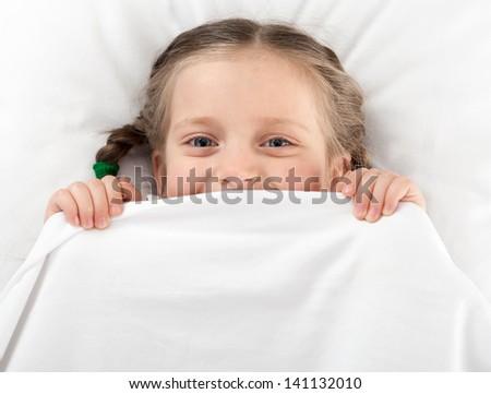 cheerful girl hiding under the blanket - stock photo