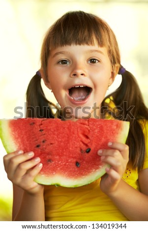 cheerful girl holding a piece of watermelon