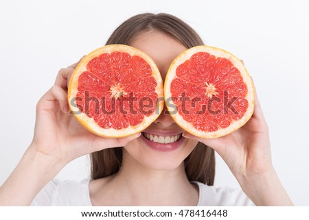 Cheerful girl holding grapefruit halves near her face pretending they are her eyes. Concept of crazy vegan person.  Mock up