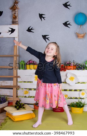 Cheerful girl in a pink dress and knitted sweater showing up on the birds