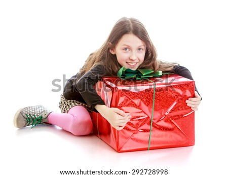 Cheerful girl in a short skirt and sneakers sitting on the floor clutching the box - isolated on white background - stock photo