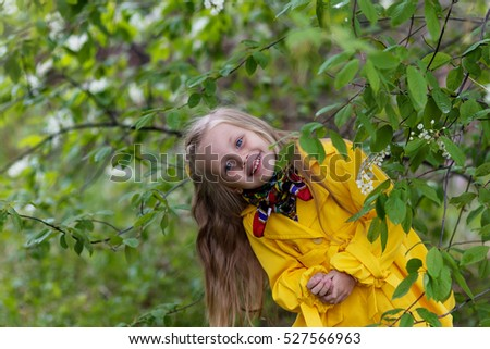 cheerful girl in a yellow raincoat on a sunny spring day