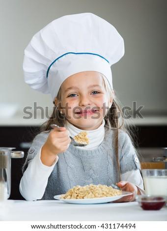 Cheerful girl in cook cap eating porridge and drink milk   - stock photo
