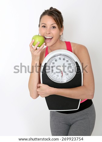 Cheerful girl in fitness outfit holding scale and green apple - stock photo