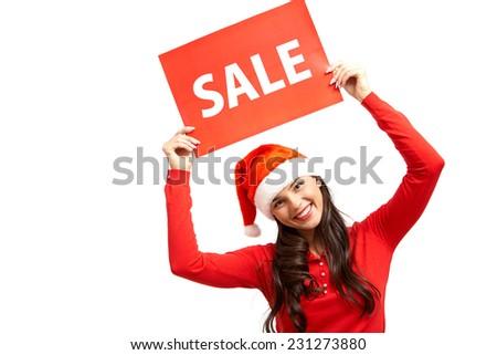 Cheerful girl in Santa cap announcing sale - stock photo