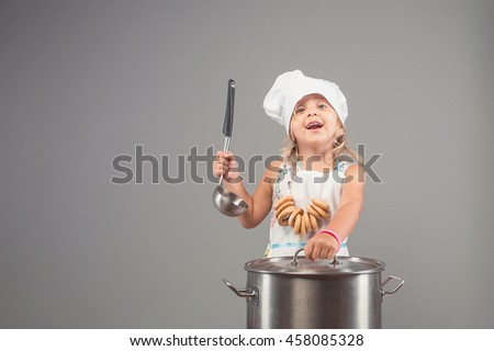 Cheerful girl in uniform chef opens the lid of the pan. The child in the kitchen preparing delicious food - stock photo