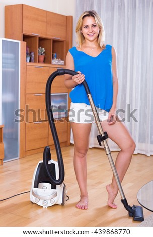Cheerful girl in white shorts vacuuming floor and furniture - stock photo