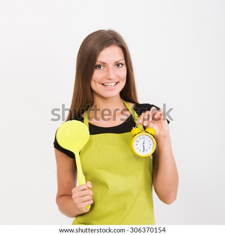 Cheerful girl in yellow apron holding a spatula and an alarm clock - stock photo