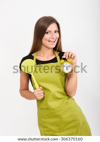 Cheerful girl in yellow apron holding a spatula and an alarm clock