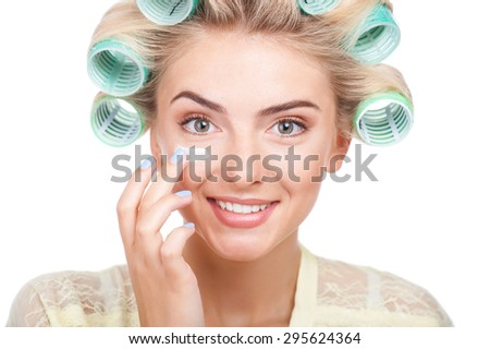 Cheerful girl is applying cream on her face. She is smiling with pleasure. She has rollers in her hair. Isolated on background - stock photo