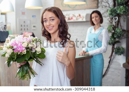 Cheerful girl is buying a cute bouquet in flower shop. She is holding it with joy and giving thumb up positively. She is smiling. The florist is standing with pretty smile on the background  - stock photo