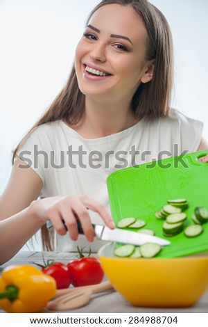 Cheerful girl is cooking healthy salad with pleasure. She is pouring chopped vegetables in a bowl and smiling. Isolated on a white background - stock photo