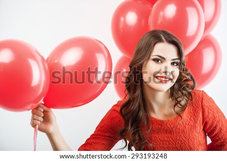 Cheerful girl is holding red balloons and resenting it to camera. She hides another balloons behind her back. The girl is smiling secretly. Isolated on grey background - stock photo