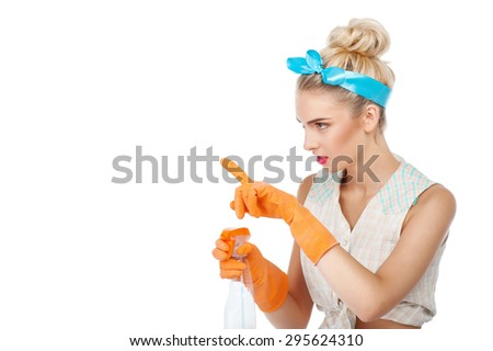 Cheerful girl is holding spray in her hand. She is pointing her index finger aside. She is looking at something with attention. Isolated on background and copy space in left side - stock photo