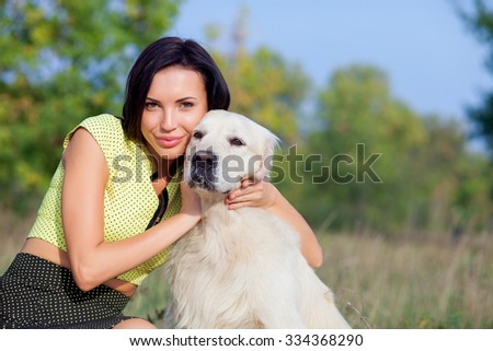 Cheerful girl is sitting near dog on grass in park. She is embracing animal with love. The lady is smiling and looking at camera happily. Copy space in right side - stock photo