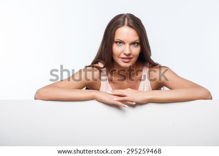 Cheerful girl is standing behind horizontal white wall. She is leaning on it with her hands. The lady is gently smiling. Isolated on background - stock photo