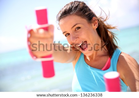 Cheerful girl lifting weights - stock photo