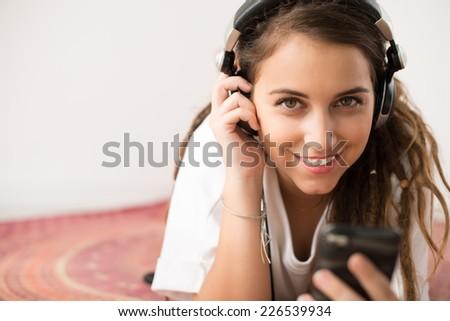 Cheerful girl listening to the music and looking at the camera - stock photo