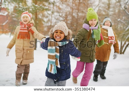 Cheerful girl looking at camera with her friends on background - stock photo