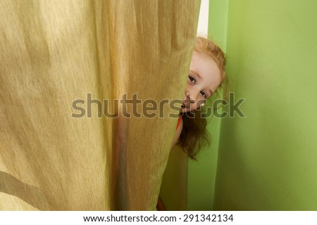 cheerful girl looks out from behind the curtains - stock photo