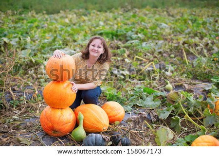 Cheerful girl on a pumpkin patch