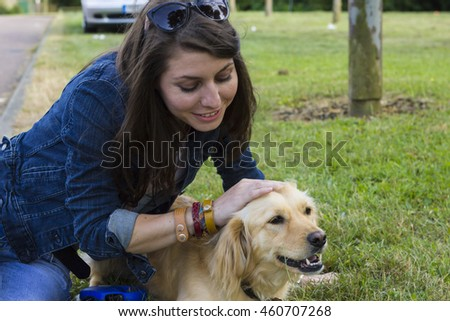 Cheerful girl on walk with golden retriever (focus on dog)