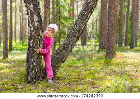 Cheerful girl plays in a forest glade. - stock photo