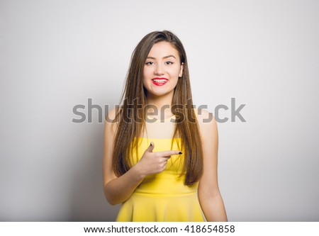 cheerful girl points a finger at someone in the side, in a yellow dress, closeup isolated on white background - stock photo