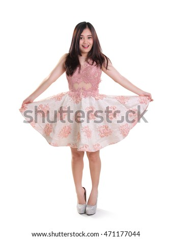 Cheerful girl posing in a dress, lifting her skirt playfully, full body shot isolated over white