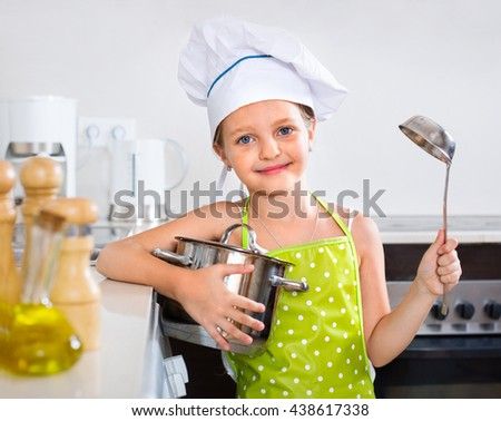 Cheerful girl posing with pan indoors - stock photo