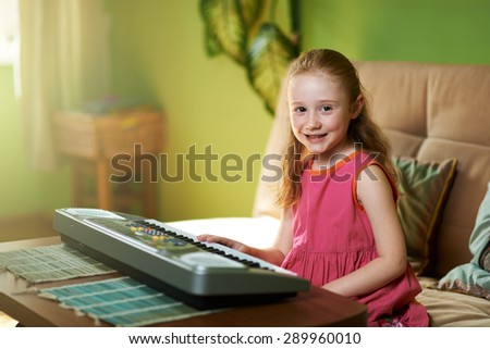 cheerful girl sits near an electronic piano - stock photo