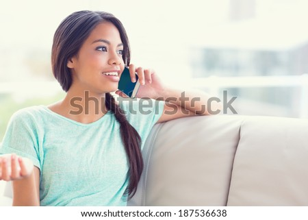 Cheerful girl sitting on sofa making a phone call at home in the living room - stock photo