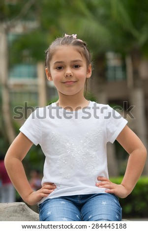 Cheerful girl sitting on the curb rests her hands on her hips - stock photo