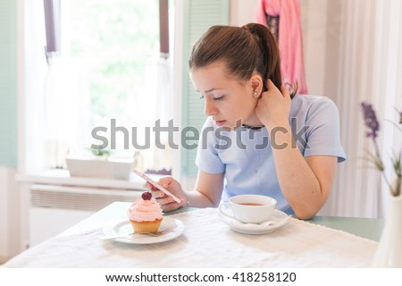 Cheerful girl smiling and laughing in the blue french cafe. Beautiful young woman eating tasty pink cupcake and white meringue and drinking a hot black tea. Blue background, window, flowers. - stock photo