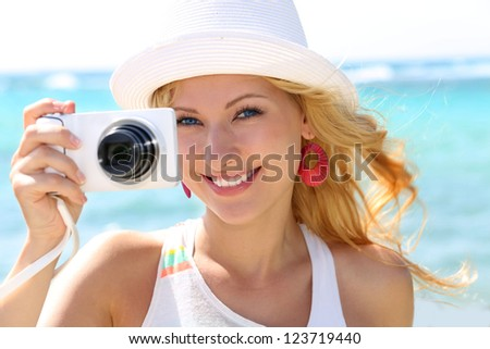 Cheerful girl talking pictures with digital camera - stock photo
