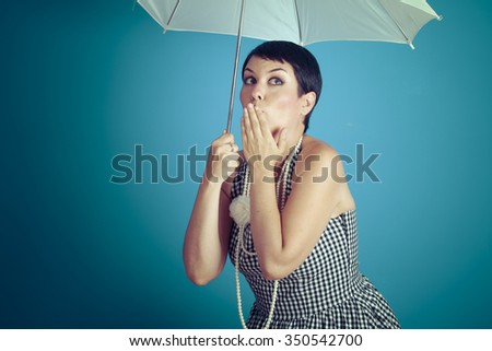 Cheerful girl vintage 50s dress with white umbrella over blue background - stock photo