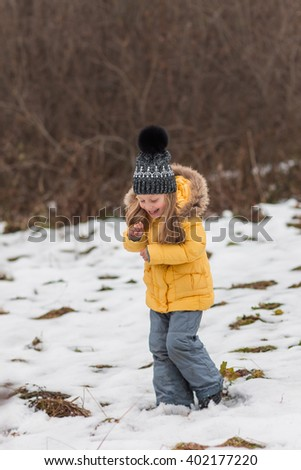 Cheerful girl walks through the woods in early spring and melted jumping on the forest - stock photo
