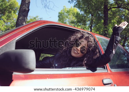 Cheerful girl waving her hand as greeting while driving a red car.Close up profile portrait. - stock photo