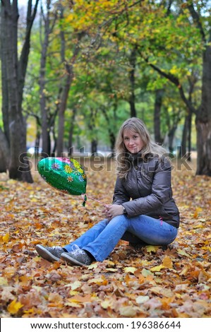 Cheerful girl with a balloon on the stump - stock photo