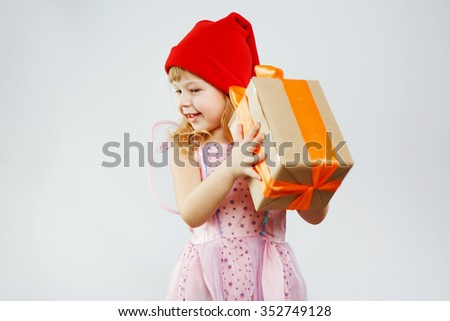 Cheerful girl, with curly blond hair, wearing on pink dress, fairy wings and red hat, posing with present in her hands, on white background, in studio, waist up - stock photo