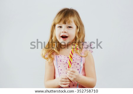 Cheerful girl, with curly blond hair, wearing on pink dress, posing with colorful candy in her hand, on white background, in studio, waist up - stock photo
