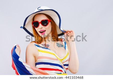 Cheerful girl with hat, striped dress and heart-shaped red sunglasses smiling widely and looking aside. Summer look. Studio, indoor, head and shoulders - stock photo
